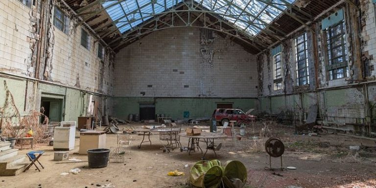 This cluttered junkyard once used to be an enormous indoor tennis court