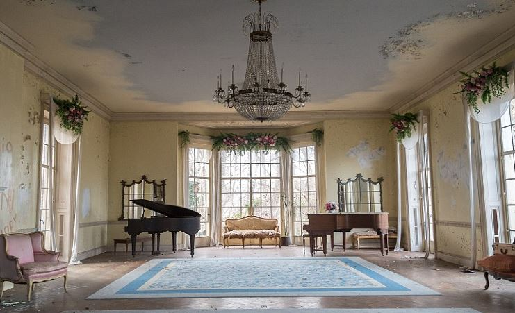 The empty ballroom hosts a giant chandelier and two grand pianos